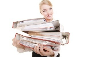 Business and paperwork. Young smiling businesswoman holding stack of folders documents. Busy woman working in office.